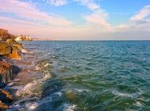 Seascape with coastal rocks and blue sky. Coastal rocks, waves and cloudy blue sky Stock Photos