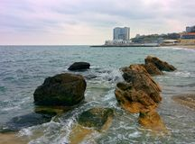 Seascape with coastal rocks and buildings Stock Photo