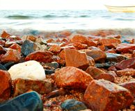 Seascape with colorful rocks, calm sea wave, fishing boat on the sea Royalty Free Stock Photo