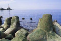 Seascape com pedras Mar e ondas azuis Terraplenagem e farol Foto de Stock Royalty Free