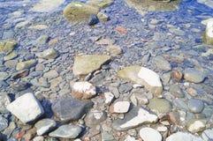 Seascape com pedras Mar e ondas azuis Terraplenagem e farol Fotos de Stock Royalty Free