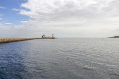 Seascape com St Elmo Breakwater Lighthouse, um navio de recipiente e um barco de motor, no porto grande, Malta imagem de stock