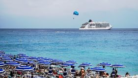 Seascape with a cruise liner, a parachute and people relaxing under striped beach umbrellas on the beach, Nice, France. A beautiful seascape with a cruise liner royalty free stock photography