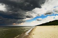 Seascape with dark, dramatic, stormy cumulonimbus cloud formation over the beach at Baltic sea. Stock Photos