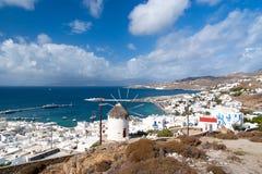 Seascape de Mykonos, Grécia Moinho de vento da vila na paisagem da montanha pelo mar azul Casas brancas no céu nebuloso com agrad Foto de Stock