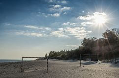 Seascape on a deserted beach with empty football goal royalty free stock photography