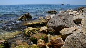 Seascape do verão Praia rochosa da água dos azuis celestes do oceano ou do mar No fundo velas de um barco de prazer Greece video estoque