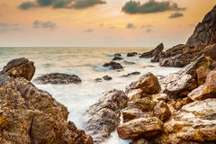 Seascape of evening wave with rock and cloud golden sky Stock Photo