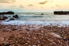 Seascape of evening wave with rock and cloud golden sky Stock Image