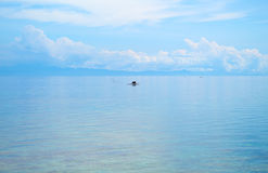 Seascape with fisherman boat and blue sky. Relaxing sea view with still seawater. Stock Photos