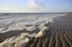 Seascape. With foam, wavy beach and sky with clouds Stock Images