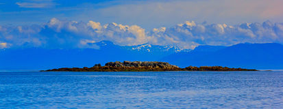 A seascape of Frederick sound, Alaska with small rocky island an Royalty Free Stock Image
