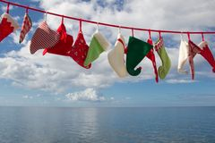 Seascape of hats and socks hanging - blue christmas background w Stock Image