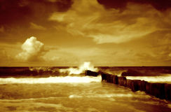 Seascape II. Seascape, artistic mode: blured and toned. Remains of the old bridge in front royalty free stock photo