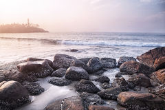 Seascape in India. View to Lighthouse on the hill from the stones near the ocean in Kovalam, Kerala, India stock photo