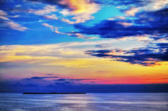 Seascape with island and clouds. Beautiful seascape with a remote island and iridescent clouds Stock Image