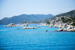 Seascape of islands and mountains around sunken city of Kekova i. N Uchagiz Antalya in Turkey with one small touristic boat Royalty Free Stock Photos