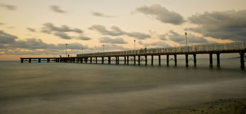 Seascape with jetty during a dramatic cloudy sunset Stock Photography