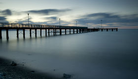 Seascape with jetty during a dramatic cloudy sunset Royalty Free Stock Image