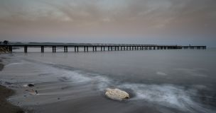 Seascape with jetty during a dramatic cloudy sunsrise Stock Photography