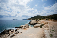 Seascape of Kalkan resort town of Turkey. Located on Mediterranean sea with rocky shore and mountains on background and sky with clouds Stock Photos