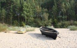 Seascape in Latvia. A wooden boat on a sandy beach in Latvia, White Dune, Saulkrasti stock photos