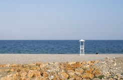 Seascape with lifeguard hut on calm sky background. Beach with lonely man stock image
