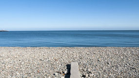 Seascape in Llandudno Wales UK. Pebble stone beach with sea defence and pier on a beautiful day in Llandudno Wales UK Stock Photography
