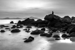 Seascape with A Lone Man Sitting on Boulders at The Beach stock images