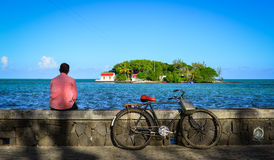 Seascape in Mahebourg, Mauritius. A man sitting and looking at the sea in Mahebourg, Mauritius. Mauritius, an Indian Ocean island nation, is known for its Royalty Free Stock Images