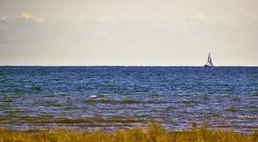 Seascape med en ensam segelbåt i avståndet arkivfoto
