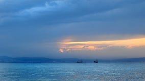 Seascape med underbara sikter av skepp, berg, havet och inställningssolen arkivfoton