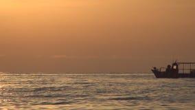 Seascape mediterrâneo com uma navigação pequena do barco de pesca em uma luz vermelha do por do sol vídeos de arquivo