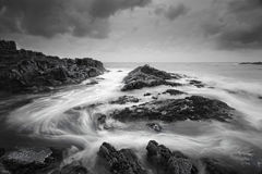 Seascape with moody weather and swirling ocean flows. Seascape at low tide with moody clouds and pending storms and swirling ocean currents around the exposed Stock Photography