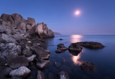 Seascape with moon and lunar path with rocks at night Royalty Free Stock Photography