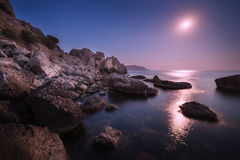 Seascape with moon and lunar path with rocks at night Royalty Free Stock Images