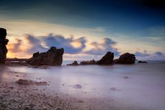 Seascape with motion wave and cloud at dawn. Seascape with natural stone arch at sunrise with motion cloud and wave in Rayong beach, Thailand. Big stopper filter royalty free stock images