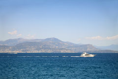 Seascape with mountains at the background and white yacht Stock Photography