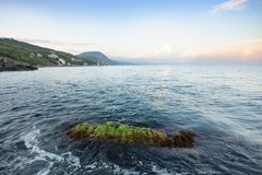 Seascape with mountains and rocky shore. stock images