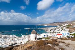 Seascape from Mykonos, Greece. Village windmill on mountain landscape by blue sea. White houses on cloudy sky with nice. Architecture. Wanderlust and travel Stock Photo