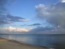 Seascape with natural rainbow. Evening seascape - rainbow, blue and white clouds over the calm sea royalty free stock image