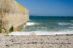 Seascape otoczaka plaży schronienia ściany niebieskie niebo Fotografia Royalty Free