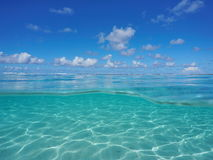 Seascape over under lagoon underwater sandy seabed. Seascape over and under sea surface, tropical lagoon with cloudy blue sky and underwater a shallow sandy Royalty Free Stock Image