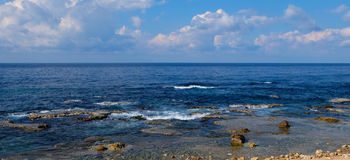 Seascape panorama - natural rock formations at the coast and clear blue water with light waves to the horizon Stock Photos
