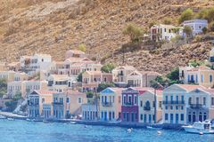 The traditional colorful houses and the port in Symi island Dodecanese, Greece. Seascape with panoramic view of the traditional colorful houses and the port stock photography