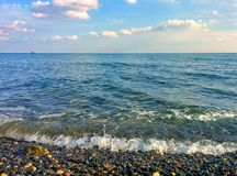 Seascape and pebble beach. Seascape, pebble beach, clouds and boat Royalty Free Stock Photos
