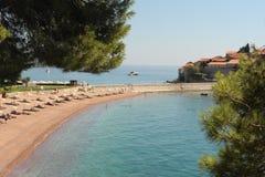 Seascape - piaskowate plaże Adriatycki morze przeciw jaskrawemu niebieskiemu niebu, chmurom i grupie hotele Aman Sveti Stefan, Mo obraz royalty free