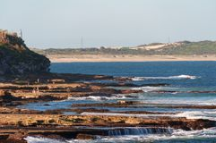 Seascape with picturesque rock formations and sandy beach on the background stock image