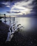Seascape of a piece of Driftwood washed up along the coastline at sunset taken with a long exposure stock images
