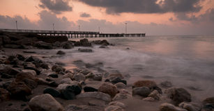 Seascape with pier and dramatic sunset Stock Photos